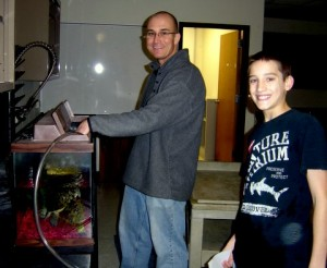 Mr. Scudder and Jacob siphoning out the water of Tungsten the Turtle's tank